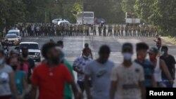 Manifestantes se alejan de los oficiales del MININT que bloquean una calle durante la protesta del 11 de julio en La Habana. (REUTERS/Alexandre Meneghini)
