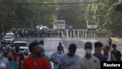 Manifestantes se alejan de los oficiales del MININT que bloquean una calle durante la protesta del 11 de julio en La Habana. (REUTERS/Alexandre Meneghini).