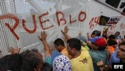 Manifestantes de la oposición venezolana gritan consignas a integrantes de la Guardia Nacional Bolivariana de Venezuela durante una marcha contra la sentencia del TSJ.