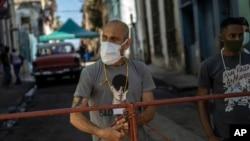 Hombres montan guardia en una reja que corta el acceso a su vecindario en cuarentena por coronavirus, en La Habana, para mantener alejados a los que no viven allí. (AP/Ramon Espinosa)
