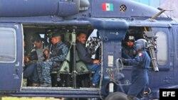 """Militares mexicanos conducen en un helicóptero al máximo dirigente del cártel de Sinaloa, Joaquín """"El Chapo"""" Guzmán (c), quien fuera detenido en el puerto turístico de Mazatlán (México), en la madrugada del sábado 22 de febrero de 2014."""