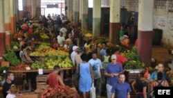 ARCHIVO. Trabajadores en un mercado ofertan sus productos.