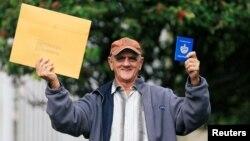 El cubano Pedro Ravelo muestra su pasaporte luego de recibir la visa de EEUU en la Embajada de EEUU en Bogotá el 22 de febrero de 2018. REUTERS/Jaime Saldarriaga