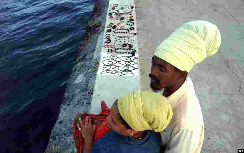Una pareja de rastafaris vende artesanías en el Malecón de La Habana (Cuba).