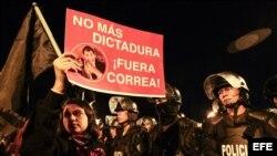 Una manifestante sostiene un cartel durante una protesta contra el Gobierno de Ecuador por dos proyectos legales sobre las herencias y la plusvalía inmobiliaria hoy, lunes 15 junio de 2015, en Quito (Ecuador). El presidente ecuatoriano Rafael Correa anunc