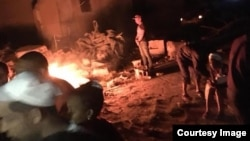 Damnificados por el tornado se calientan alrededor de una rustica fogata