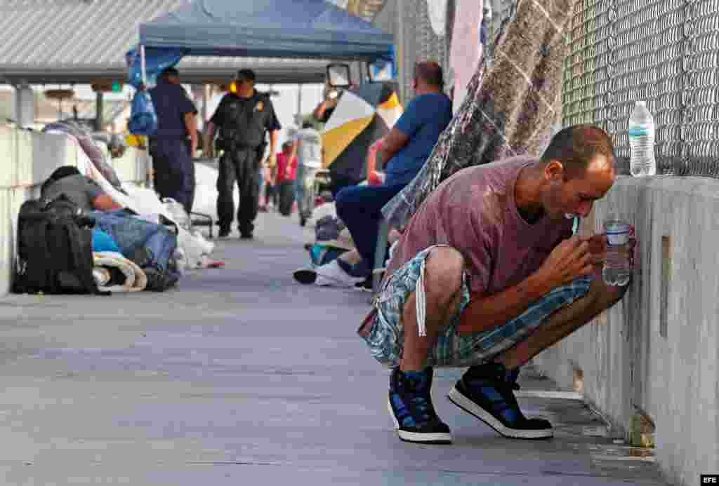 Un hombre se lava los dientes mientras aguarda en un puente junto a otros solicitantes de asilo de Guatemala y Cuba para poder entrar en EE.UU. en Matamoros (México) el 29 de junio de 2018.