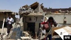 Varios yemenís intenta recuperar sus pertenencias entre los daños causados por un supuesto ataque aéreo saudí contra las milicias del movimiento chií de los hutíes en Saná, Yemen.