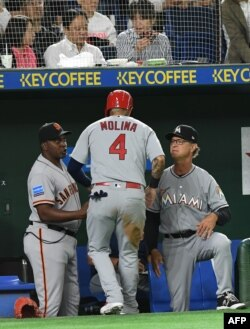El manager de la MLB All Stars, Don Mattingly, de los Miami Marlins (der.) felicita a Yadier Molina, de los Cardinals de St. Louis, en un juego de exhibición en Tokio, en noviembre de 2018.