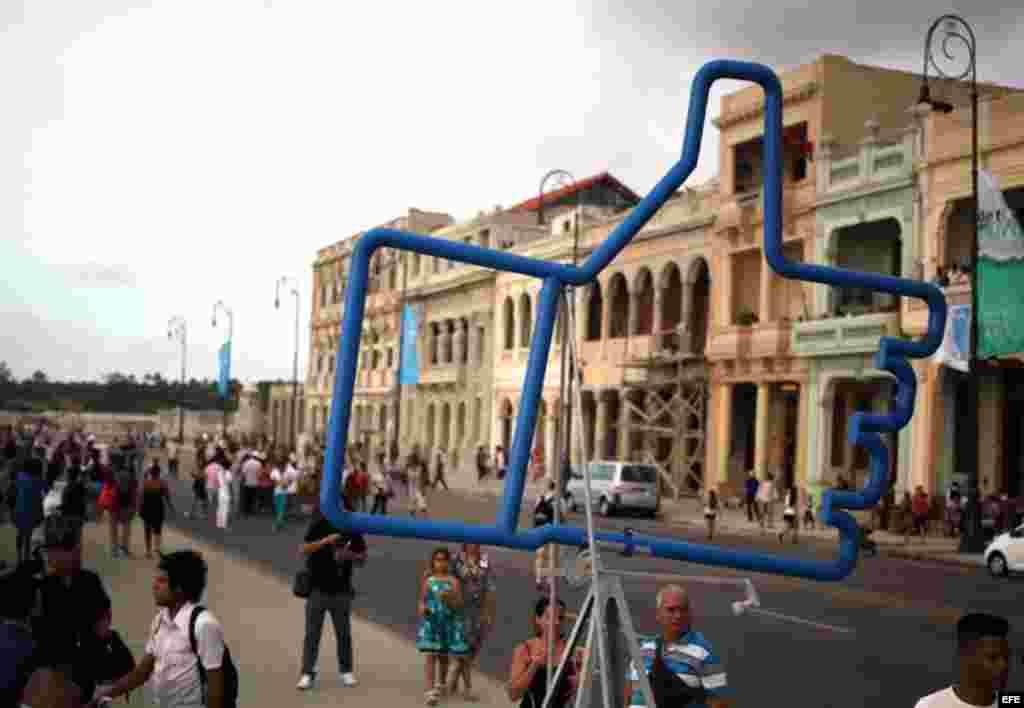 """Personas caminan junto a la obra """"Suite Emotion"""" de Alexander Guerra, expuesta en el Malecón hoy, domingo 24 de mayo, donde ha sido inaugurada la exposición """"Detrás del Muro"""" como parte de la XII Bienal de Arte de La Habana."""
