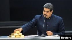 Nicolás Maduro toca una barra de oro mientras se dirige a los ministros responsables del sector económico en el Palacio de Miraflores.