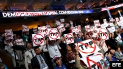Delegados sostienen carteles contra el Acuerdo Estratégico Trans-Pacífico (TPP).