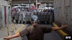 Un hombre protesta frente a miembros de la Policía Nacional Bolivariana. (Archivo)