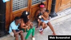 Mujeres sentadas con niños en brazos, a un lado de la calle Obispo, en la Habana Vieja. Foto: Ana León.