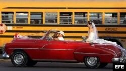 Una pareja de recién casados viaja en un viejo auto descapotable.