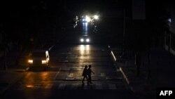 Transeúntes cruzan a oscuras el lunes una calle de Caracas, iluminados solamente por los focos de un vehículo (Foto: AFP).