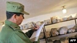 En esta foto de archivo tomada en 2005 un oficial cubano registra un cargamento de drogas incautado en Holguín.