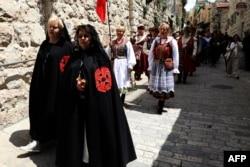 Damas de la orden de los Caballeros del Santo Sepulcro caminan por la Vía Dolorosa, en Jerusalén, durante la procesión del Viernes Santo. .