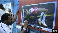 El plusmarquista mundial cubano de salto de altura Javier Sotomayor firma una fotografía.