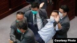 Los guardias de seguridad arrastran al legislador pro democracia Ray Chan durante una reunión legislativa el 8 de mayo en Hong Kong.