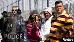 Un grupo de cubanos esperan ante agentes de seguridad de frontera en Ciudad Juárez.
