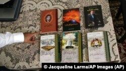 Kamaltürk Yalqun muestra los libros de su padre en abril de 2019 en Filadelfia. Yalqun Rozi, encarcelado en la República Popular China, dedicó su vida a la literatura y la educación uigures. Foto: © Jacqueline Larma/AP Images.
