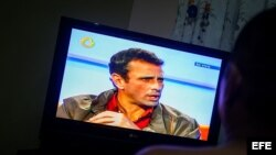 Un hombre observa la transmisión de una entrevista con el canal privado Globovisión a Henrique Capriles.