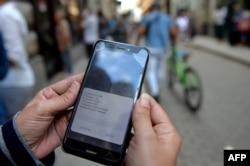 Una mujer chequea las opciones para conectarse a Internet en Cuba.