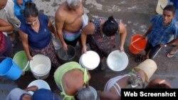 Vecinos hacen cola para abastecerse de agua potable.
