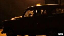 Un taxista espera a un cliente en un auto de la década de los 50 en una calle de La Habana, Cuba.