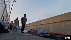 Varias personas que se dirigen a cruzar la frontera pasa delante de varios solicitantes de asilo de Guatemala y Cuba que esperan en un puente a poder entrar en EEUU. (Archivo)