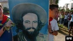 Un grupo de niños cubanos se dirige a depositar flores en el mar en homenaje a Camilo Cienfuegos.