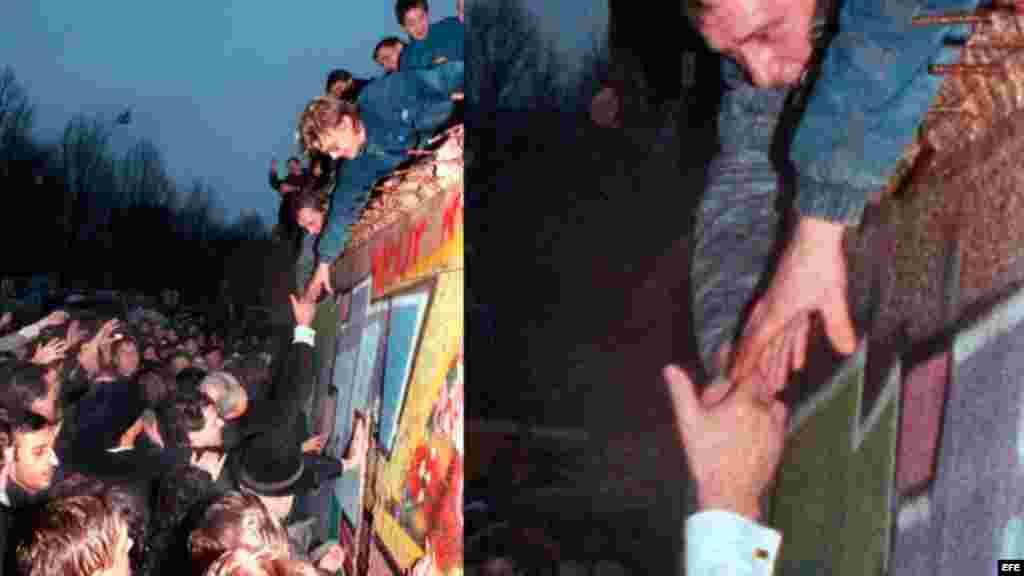 El canciller alemán, Helmut Kohl (c), estrecha la mano a un ciudadano berlinés que se encuentra encaramado en lo alto del Muro de Berlín cerca de la Puerta de Brandemburgo, en Berlín (Alemania).