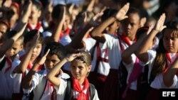 Alumnos de una escuela primaria saludan la bandera cubana, en La Habana.