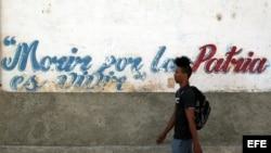 Un joven camina junto a un muro con un frangmento del himno nacional de Cuba.