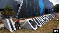 Un trabajador pinta una parte de un letrero de la II Cumbre de la Comunidad de Estados Latinoamericanos y del Caribe (Celac).