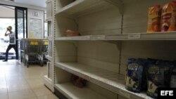Un hombre ingresa a un supermercado con estanterías desabastecidas en Caracas.