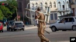 Un hombre carga un utensilio de trabajo en La Habana el 27 de junio de 2019. (AP).