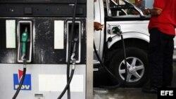 Un par de hombres trabajan en una estación de servicio de gasolina en Caracas.