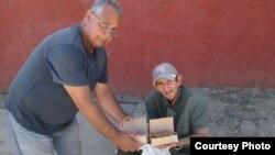 El promotor del proyecto Capitán Tondique, Francisco Rangel Manzano, entrega comida a un desamparado en Colón, Matanzas.