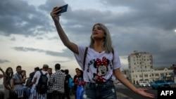 Una joven youtuber cubana graba un video en el Malecón habanero.