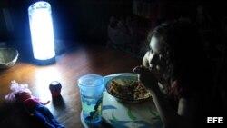 Niña come alumbrada por una lámpara de baterías durante un apagón. (Archivo)