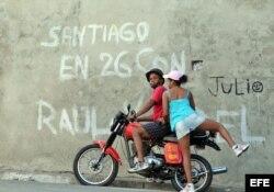 Una mujer se sube en una moto en la ciudad de Santiago de Cuba.