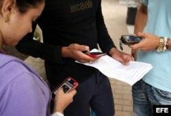 Tres jóvenes usan sus teléfonos móviles en La Habana.