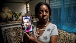 Mayda Yudith Sotolongo sostiene una foto de su hijo, Yunir Consuegra, joven discapacitado detenido el 11J. (YAMIL LAGE / AFP)