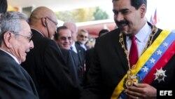 Fotografía cedida por Prensa Miraflores del presidente de Venezuela, Nicolás Maduro (d), saluda a Raúl Castro durante el desfile militar para conmemorar el primer aniversario del la muerte del fallecido mandatario venezolano Hugo Chávez.
