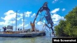 Un casco de acero de 18 pies es sacado de los manglares de las Marquesas. (Foto: Celia Hitchins/Monroe County Marine Resources Office)