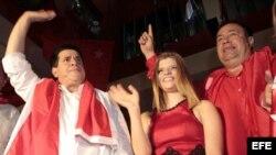 El presidente paraguayo electo, Horacio Cartes (i), saluda a seguidores junto a su vicepresidente, Juan Afara (d), y acompañado de su hija Sol (c).