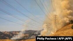 Líneas eléctricas amenazadas fue las llamas en California, 26 de octubre de 2019.