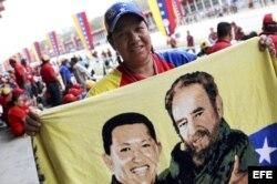 Un hombre muestra una bandera venezolana con el rostro de Hugo Chávez junto al de Fidel Castro, en el Paseo de Los Próceres, en Caracas, antes de que sus restos mortales sean trasladados al Museo Militar de la ciudad